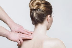 A doctor pressing on the neck to relieve pain